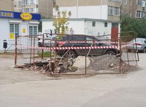 Первое обещание выполнено: наполненную водой и мусором огромную яму огородили забором и красной лентой