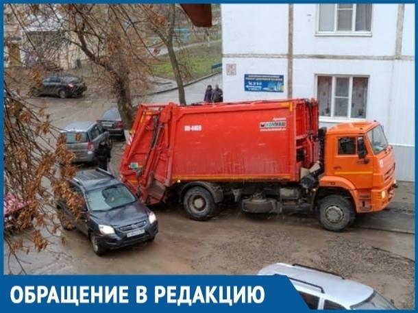 Объезжая засыпанную яму, мусоровоз застрял в сливном лотке во дворе на Строителей