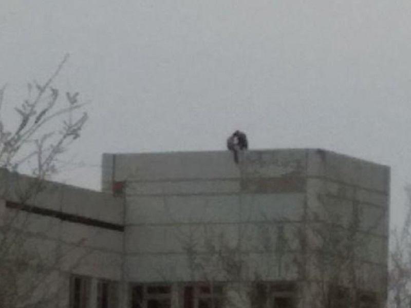 Подростки опасно свесили ноги с крыши недостроенной больницы на Гагарина