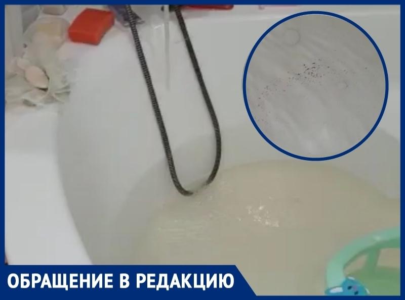 Желтая вода с мелкими камешками льется из крана в доме на улице Закурганной